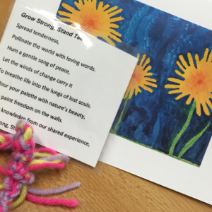 A card with sunflowers painted on it, a laminated poem, and a friendship bracelet.