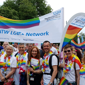 Members of the CNTW LGBT+ Staff Network at last year's Newcastle Pride event. They are wearing lots of rainbow accessories and holding a CNTW LGBT+ Network banner.