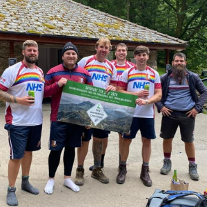 6 men in rugby shirts with rainbows and 'thank you NHS' on stand together in a cap park, holding a banner for the 5 Wainwrights challenge