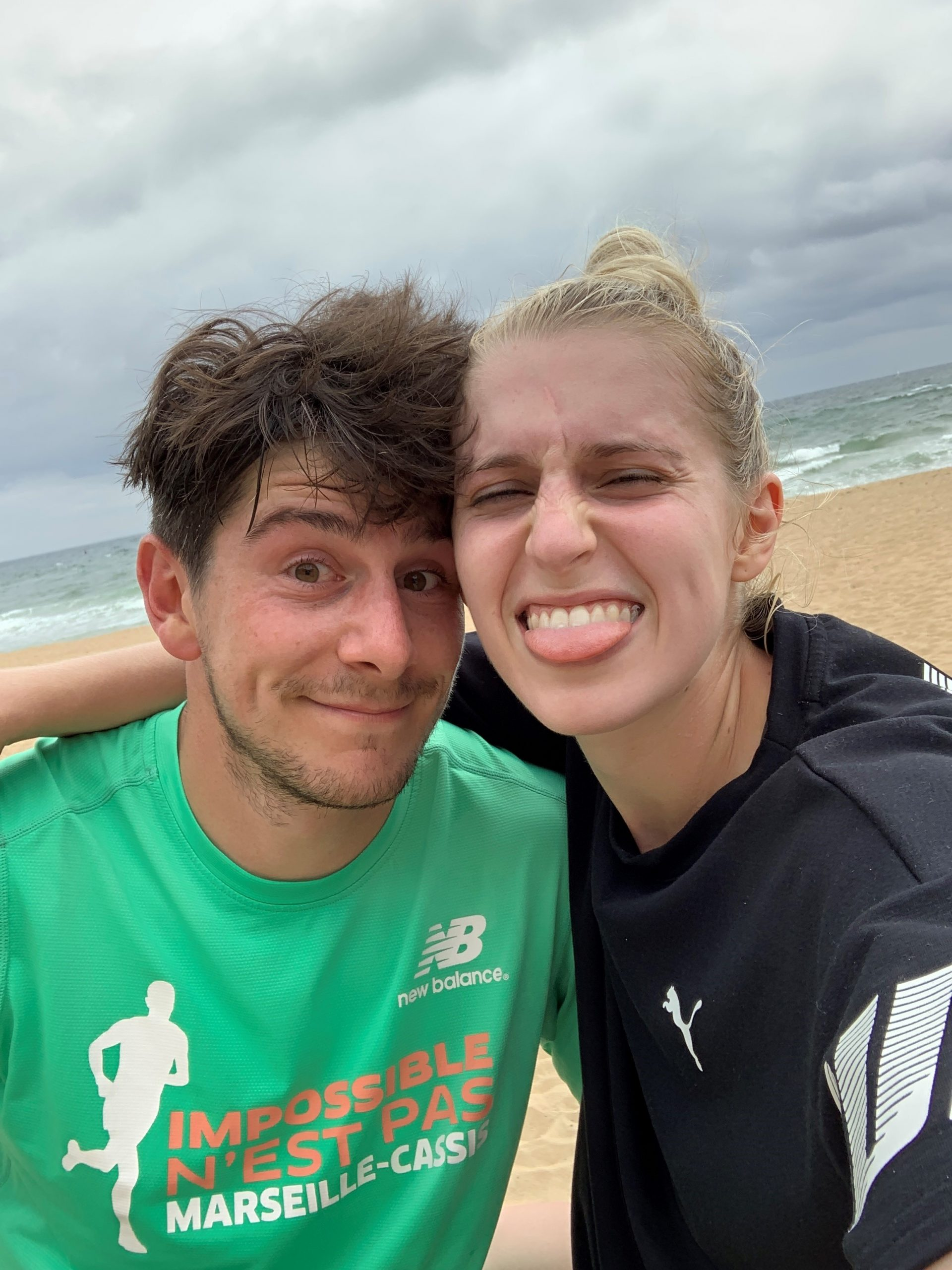 Abi and Alex taking a selfie together on a windswept beach