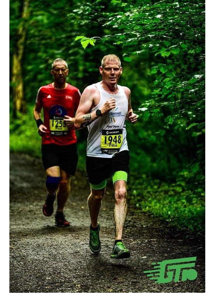 Paul Sams running in a race through woodland